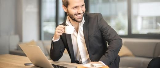 man-holding-white-teacup-in-front-of-gray-laptop-842567
